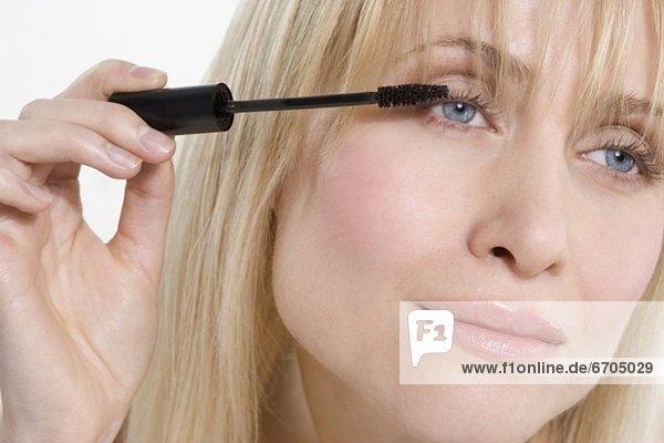 eincremen  verteilen  Frau  sehen  Wimperntusche  Seitenansicht  auftragen