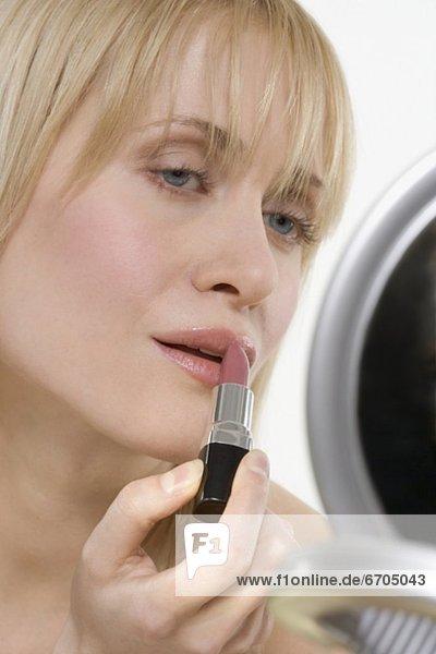eincremen verteilen Frau Lippenstift auftragen Spiegel mund