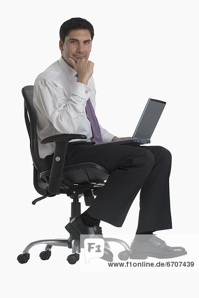 Businessman holding laptop in chair