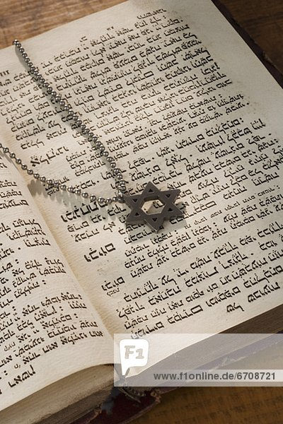 Star of David necklace on book with Hebrew text