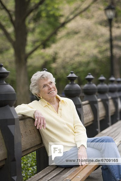 Portrait of woman sitting on park bench