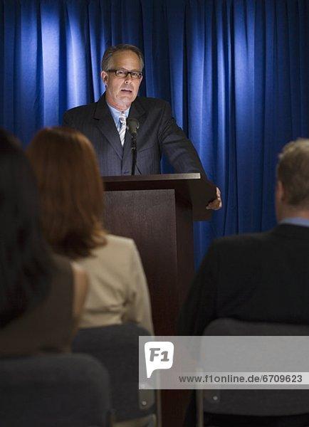 Geschäftsmann spricht am Rednerpult