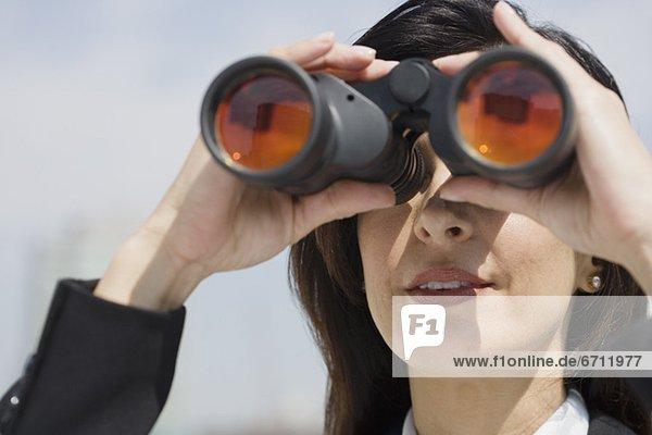 Geschäftsfrau schaut durch Fernglas