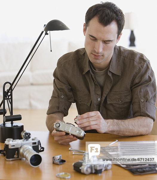 Mann  zusammenbauen  Blick in die Kamera  Tisch