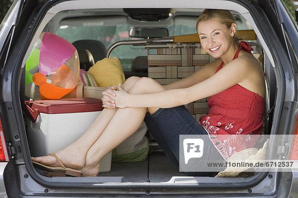 Frau sitzt auf der Rückseite des Autos