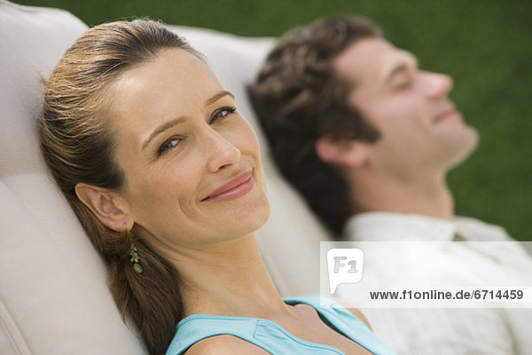 Paar liegt auf Liegestühlen