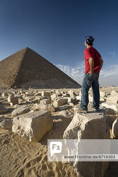 A Man Standing Near A Pyramid In The Desert