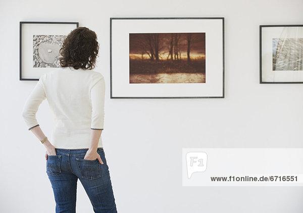 Woman looking at art in art gallery
