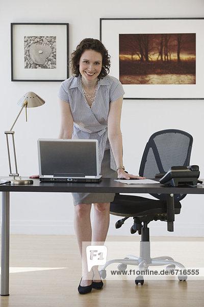 Geschäftsfrau stützte sich auf Schreibtisch