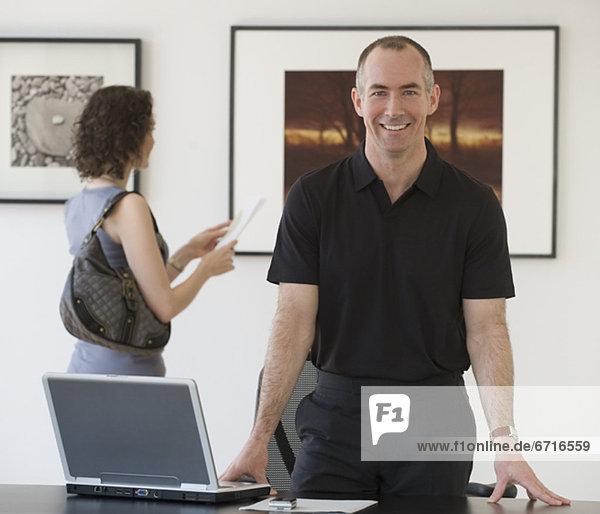 Kaufmann lehnend auf Schreibtisch