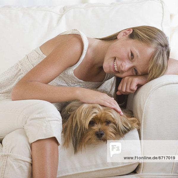 Girl hugging dog on sofa