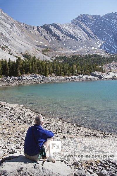 sitzend  nebeneinander  neben  Seite an Seite  Berg  Mann  See