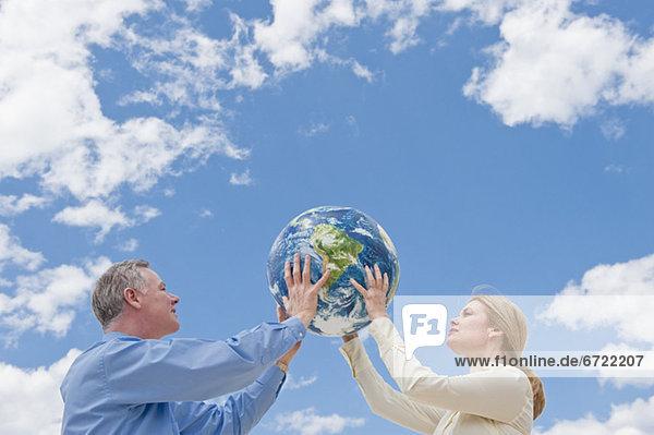 Zwei Leute halten bis ein globe Zwei Leute halten bis ein globe