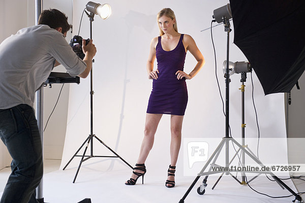 Photographer taking picture of model in studio