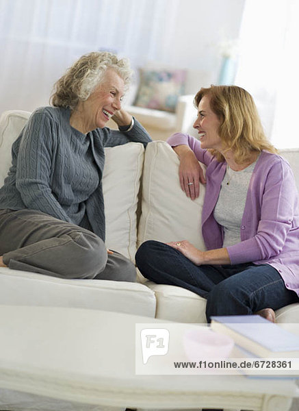 USA  New Jersey  Jersey City  Mother and daughter talking on sofa