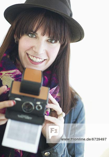 Porträt der jungen Frau mit Instant-Kamera