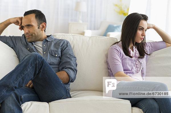 Couple sitting on sofa back to back