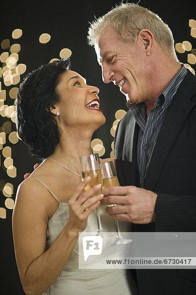 Reifen Sie Paar stößt an mit champagne