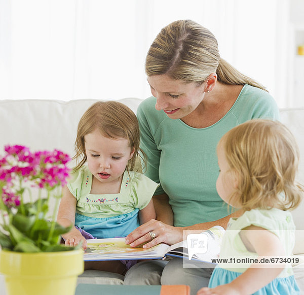 Mother with daughters (2-3) reading book on sofa