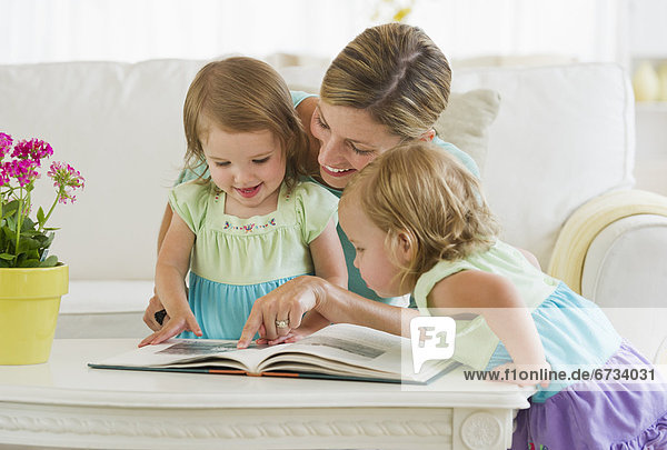Mother with daughters (2-3) reading book in living room