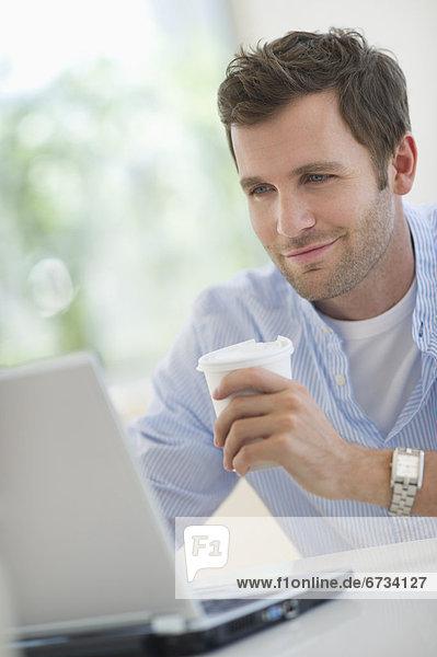 benutzen  Mann  Notebook  jung  trinken  Kaffee