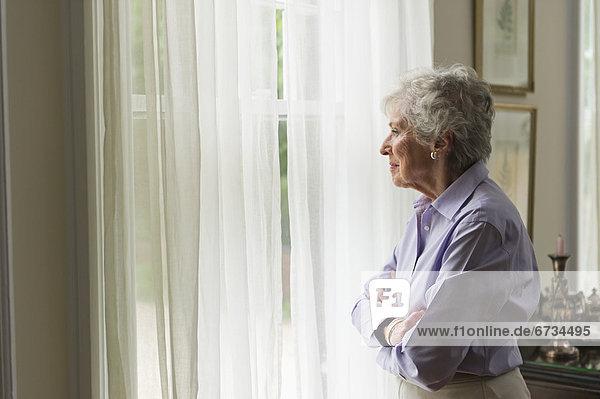 ältere Frau looking durch Fenster