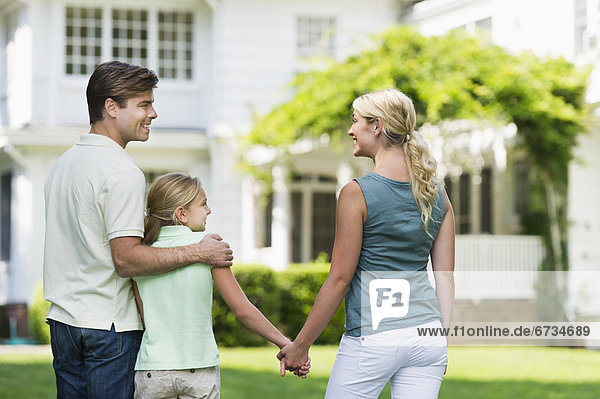 Parents with daughter (10-11) in front of house