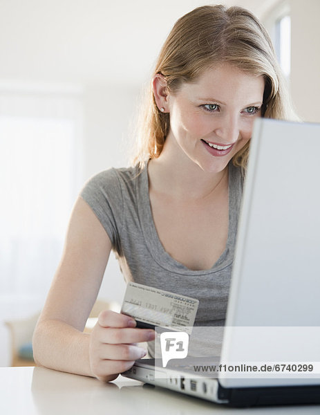 Young woman with laptop and credit card