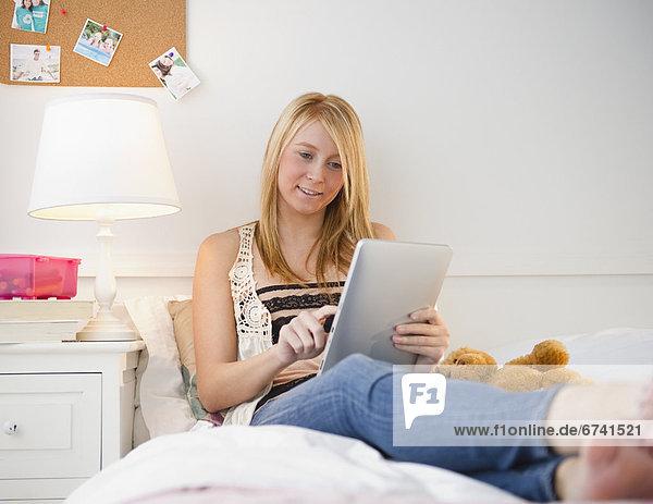 Vereinigte Staaten von Amerika USA sitzend benutzen Frau Bett Tablet PC