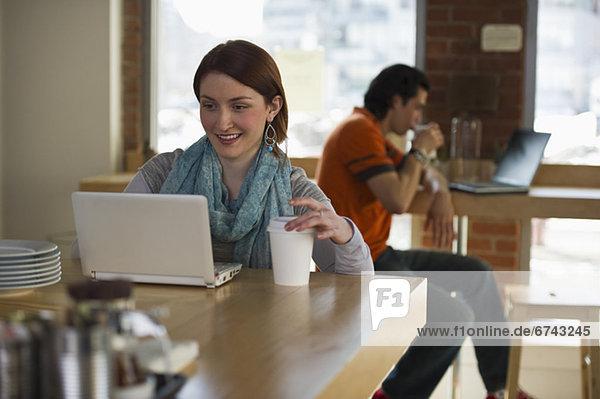 Frau Notebook arbeiten Laden Kaffee