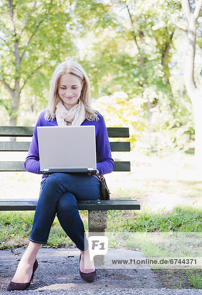 Vereinigte Staaten von Amerika  USA  sitzend  benutzen  Frau  New York City  Notebook  Sitzbank  Bank  jung  Central Park  Manhattan