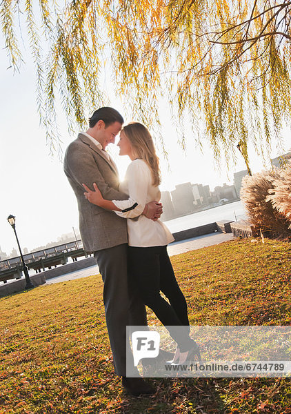 USA  New York  Long Island City  Young couple embracing in park
