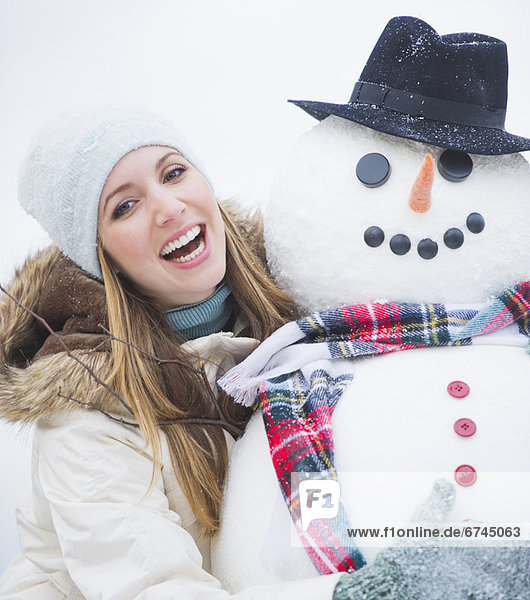 Portrait of young woman with snowman