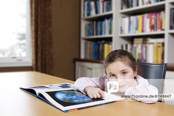 Young Girl Sitting in Library Reading Book  Toronto  Ontario