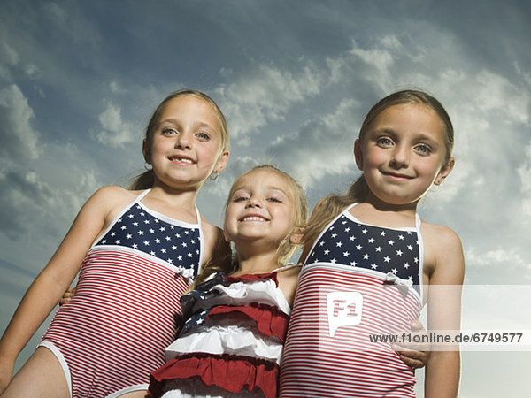 Three young sisters hugging