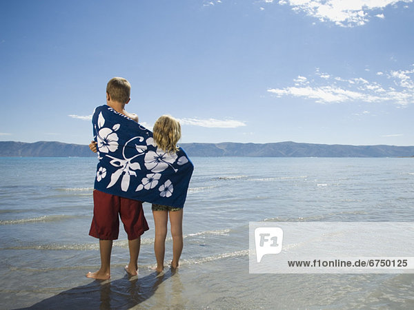 Brother and sister wrapped in beach towel  Utah  United States