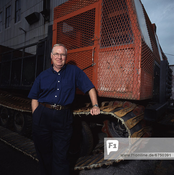 Portrait of Man Standing next to Tractor