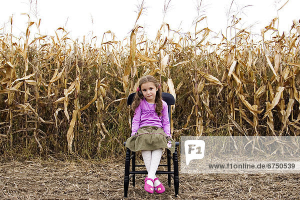 Young Girl Sitting on Chair in Corn Field