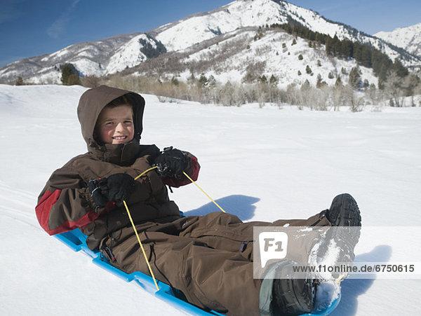 Boy riding on sled