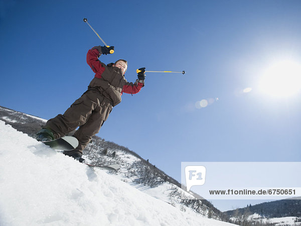 Boy with arms raised on skis