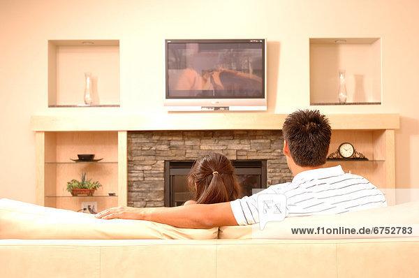 sitzend  sehen  Menschlicher Vater  Fernsehen  Couch  Tochter