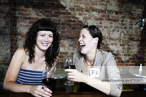 Female Friends Laughing Over Drinks