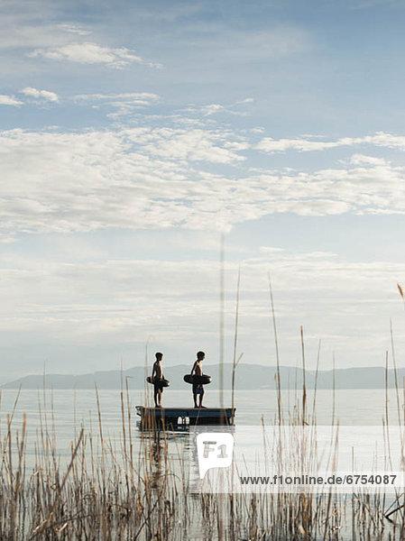 Boys (10-11 12-13) jumping from raft