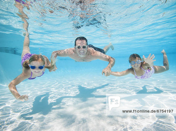Father with two daughters (6-7 8-9) swimming underwater