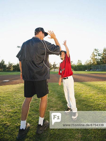 USA  California  Ladera Ranch  man and boy (10-11) on baseball field