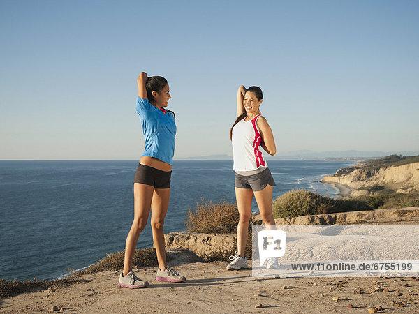 USA  California  San Diego  Two women stretching on beach