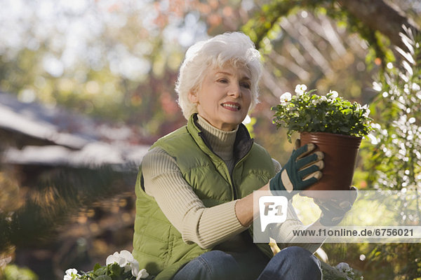 Senior woman sitting in domestic garden holding potted plant