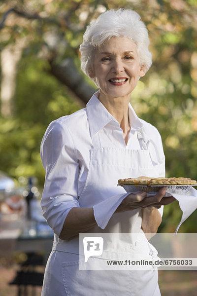 Senior woman standing in garden holding pie