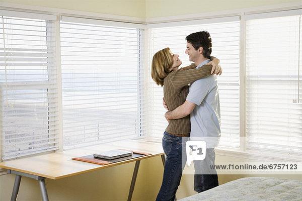 Paar umarmt neben Fenster