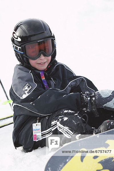 Boy Snowboarder Sitting on Slope  Alberta Rocky Mountains